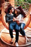 Полюбите портрет ласковой молодой пары лежа на гамаке смотря прочь усмехающся Романтичный сад человека и женщины внутри Стоковое Изображение