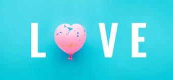Полюбите текст с розовой формой сердца воздушного шара на голубой предпосылке Стоковое фото RF