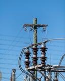 Поляки и изоляторы трансформаторов на станции силы электрической под стоковое фото