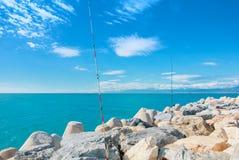 Поляки рыболовных удочек стоя на больших камнях на пристани на солнечном d Стоковые Фото