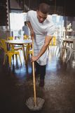 Пол кельнера mopping в кафе Стоковые Изображения RF