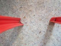 Пол красочной пастельной каменной картины белый, с пакостными красными пластичными ногами стула Стоковые Изображения