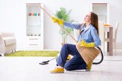 Пол чистки молодой женщины дома делая работы по дому стоковая фотография