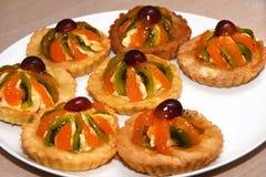 Помадка испечет с сливк и кусками плодоовощ виноградин, кивиа, апельсина на белой плите стоковая фотография rf
