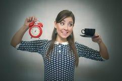 помадка чашки круасанта кофе пролома предпосылки кофе больше времени Перерыв на ланч Девушка с чашкой кофе и красным будильником Стоковое Фото