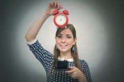помадка чашки круасанта кофе пролома предпосылки кофе больше времени Перерыв на ланч Девушка с чашкой кофе и красным будильником Стоковые Изображения RF