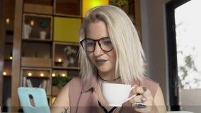 помадка чашки круасанта кофе пролома предпосылки Женщина используя smartphone пока выпивающ кофе Стоковое фото RF