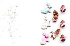 Помадки для таблицы пасхи Яичка шоколада около печений в форме зайчика пасхи на белом космосе экземпляра взгляд сверху предпосылк Стоковое фото RF