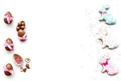 Помадки для таблицы пасхи Яичка шоколада около печений в форме зайчика пасхи на белом космосе экземпляра взгляд сверху предпосылк Стоковое Изображение RF