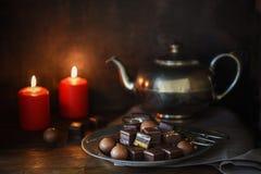 Помадки шоколада рождества, 2 красных свечи и серебряного teapott стоковые фотографии rf