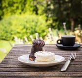 Помадка испечет на деревенском столе с чашкой кофе в саде Стоковое Фото