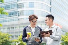 помадка чашки круасанта кофе пролома предпосылки 2 жизнерадостных бизнесмена говоря пока одно из Стоковая Фотография