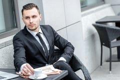 помадка чашки круасанта кофе пролома предпосылки Молодой бизнесмен держа чашку кофе в руке Стоковые Изображения