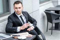помадка чашки круасанта кофе пролома предпосылки Молодой бизнесмен держа чашку кофе в руке Стоковая Фотография RF