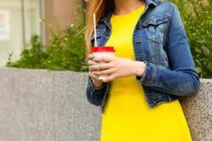 помадка чашки круасанта кофе пролома предпосылки Портрет девушки в красивых желтых платье лета и куртке джинсов отдыхает с кофе в Стоковые Изображения RF