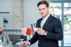 помадка чашки круасанта кофе пролома предпосылки Уверенно и успешный бизнесмен стоя в a Стоковые Изображения