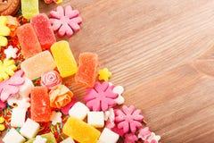 Помадки и конфеты на деревянном столе Стоковое фото RF