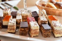 Помадки и торты аранжированные на таблице Стоковая Фотография RF