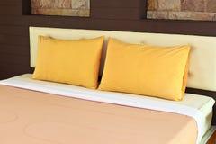 Померанцовые подушки на кровати стоковое изображение