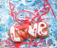Пометьте буквами печенья на день ` s валентинки или на день свадьбы на предпосылке заполнителя сини и белой бумаги Стоковые Изображения RF