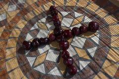 Пометьте буквами x сделанный с cherrys для того чтобы сформировать букву алфавита с плодоовощами стоковая фотография