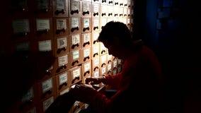помещает руки в архив шкафа заполняя ища студента Студент силуэта сток-видео