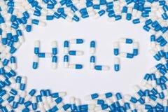 Помогите тексту слова сделанному голубых таблеток, пилюлек и капсул стоковые фотографии rf