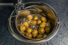 Помойте сырцовые картошки в раковине Символизирует сельскую домашнюю кухню стоковая фотография rf