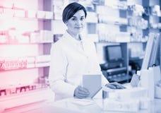 Помощь женского аптекаря предлагая на счетчике в фармации Стоковое фото RF