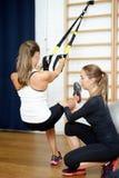 Помощь инструктора спорт для того чтобы сделать тренировку на trx веревочки подвеса Стоковое Изображение RF