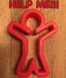 Помощь красного человека хотеть на деревянной предпосылке Стоковое Фото
