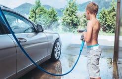 Помощь мальчика для того чтобы помыть автомобиль Стоковое Изображение