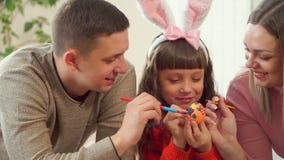 Помощь мамы и папы ее дочь украсить пасхальное яйцо с щетками счастливая семья совместно подготавливая для пасхи акции видеоматериалы