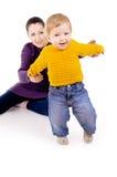 Помощь матери для того чтобы сделать первые шаги ребенка Стоковое Изображение RF