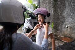 Помощь матери ее ребенок для того чтобы положить дальше шлем стоковая фотография