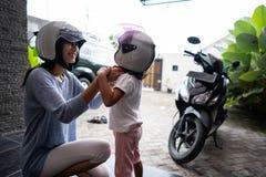 Помощь матери ее ребенок для того чтобы положить дальше шлем стоковые фотографии rf