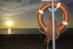 Помощь пловучести спасателя на пляже на восходе солнца Стоковое Изображение RF