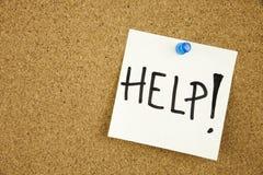 помощь - слово рукописное на стоге липких примечаний вывешенных на доску объявлений пробочки Стоковое фото RF