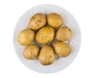 Помытые сырцовые картошки в стеклянной пластинке изолированной на белизне Стоковые Изображения