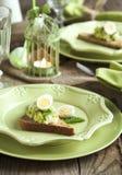 Помятые сандвичи яичка и авокадоа на праздничной таблице пасхи Стоковое Изображение