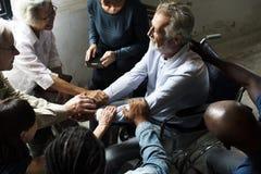 Поощрение группы людей к старшему человеку стоковая фотография