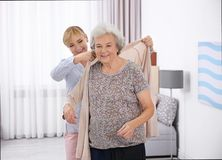 Попечитель помогая старшей женщине положить дальше кардиган стоковые фото
