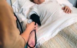 Попечитель проверяя кровяное давление к старшей женщине стоковые изображения