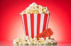 Попкорн в большой квадратной коробке и вокруг, билет кино на ярком r стоковые изображения