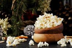 Попкорн в деревянной плите на предпосылке рождества Стоковые Фотографии RF