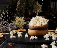 Попкорн в деревянной плите на предпосылке рождества Стоковая Фотография RF