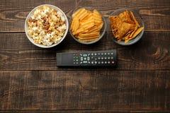 Попкорн, обломоки и ТВ Tortilla удаленные на коричневой деревянной предпосылке концепция смотреть фильмы дома над взглядом стоковое фото rf