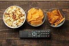 Попкорн, обломоки и ТВ Tortilla удаленные на коричневой деревянной предпосылке концепция смотреть фильмы дома над взглядом стоковое фото