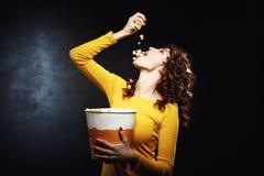 Попкорн привлекательной молодой женщины лить в рте держа большое ведро Стоковое Фото
