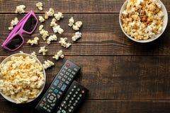 Попкорн, стекла 3D и ТВ удаленные на коричневой деревянной предпосылке концепция смотреть фильмы дома над взглядом стоковые фото